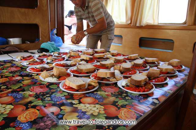 Bread, tomato, olives, feta cheese, cheesepie and spinach pie for lunch and for those daring raki to drink FOLEGANDROS PHOTO GALLERY - Lunch on board by Ioannis Matrozos